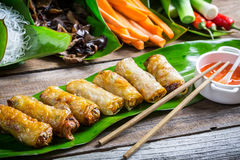 Fried spring rolls surrounded by ingredients. On old wooden table Stock Photos