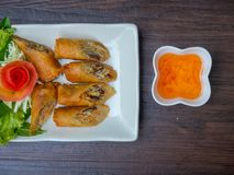 Fried spring rolls and sweet sauce. Fried spring rolls with vegetables and sweet sauce on wooden background Stock Photo