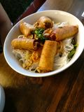 Fried spring rolls on white rice noodles. Fried meat spring rolls with white rice noodles called Bun in a vietnamese restaurant specialized in Hue food from Stock Photo