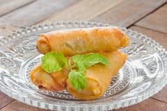 Fried Spring rueda la comida en el plato cristalino, fondo de madera Imágenes de archivo libres de regalías