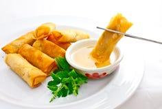 Fried springroll dip into sweet plum sauce. Taken by chopsticks Royalty Free Stock Image