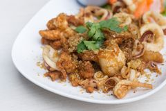 Fried squid with garlic in white dish on the table stock image