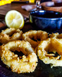 Fried Squid with lemon at the restaurant. Seafood concept Stock Images