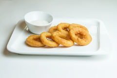 Fried squid rings breaded. Calamari rings with a creamy sauce on a white plate stock image