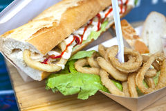 Fried squid rings displayed on bread roll and cardbox. Popular spanish snack Royalty Free Stock Images