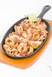 Fried Squid Rings. Pan  with red pepper Stock Photo