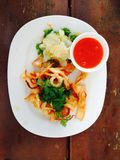 Fried squid and salad in white plate. On wooden table stock photos