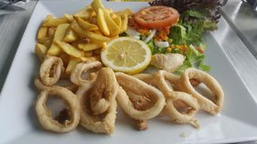 Fried squid. Served in a pottery fish with French fries and tomato salad and lettuce Stock Photo