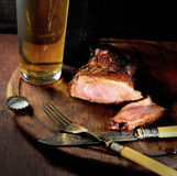 Fried steak with aromatic spices, beer, vintage fork and knife on a wooden background Stock Image