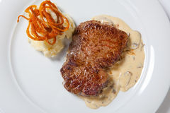 Fried steaks with potatoes, fried onion and cream sauce. Royalty Free Stock Photography