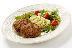 Fried steaks with potatoes and vegetables Royalty Free Stock Photography