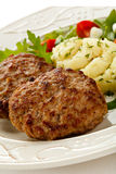 Fried steaks with potatoes and vegetables Stock Images