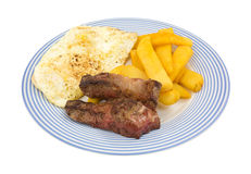 Fried strip steak and eggs with potatoes on blue striped plate Royalty Free Stock Photos