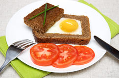 Fried  sunny-side-up egg. Fried egg in toast with tomato on white plate Royalty Free Stock Images