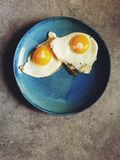 Fried sunny-side up eggs shot top down on blue plate Stock Photos