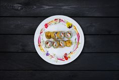 Fried sushi with a cucumber, some cream cheese, tobiko caviar, salmon and eel. Top view. Black wooden background. Fried sushi with a cucumber, some cream cheese Royalty Free Stock Photography