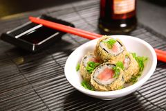 Fried sushi foursome. Hot sushi roll Tekke tempura, tuna, spicy sauce, cucumber on restaurant table Royalty Free Stock Image