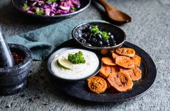 Fried sweet potato slices served with sour cream dip, black olives and salad royalty free stock images