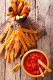Fried sweet potato wedges with herbs and ketchup close-up. verti Stock Photos