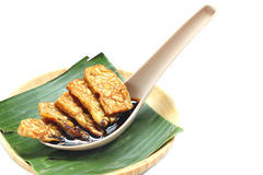 Fried tempeh for snack. On banana leaf. Made by a natural culturing and controlled fermentation process that binds soybeands into a cake form Royalty Free Stock Photos