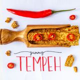 Fried tempeh in a wooden scoop decorated with chilly. YUMMY TEMPEH caption. Top view. Pieces of fried tempeh, Indonesian soy product. YUMMY TEMPEH caption. Top royalty free stock images