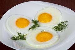 Fried three eggs. Served dill stock photos