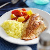 Fried tilapia filet with yellow rice Stock Image