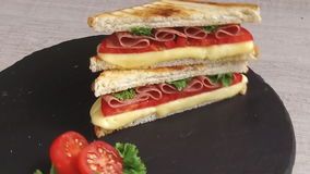 Fried toast with cheese  tomato salami on a stone surface rotate stock video