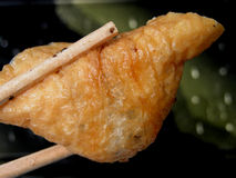 Fried tofu. A piece of fried tofu and two chopsticks Stock Image