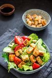 Fried Tofu Salad. With Cucumbers, Tomatoes, Avocado and Sesame Seeds. Homemade asian vegetable and tofu salad in ceramic bowl on black stone background. Healthy Royalty Free Stock Photo