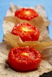 Fried tomato halves. On sheets of brown paper in a row Royalty Free Stock Photos
