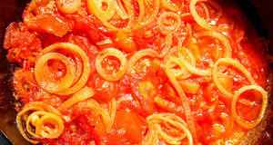 Fried tomatoes. With oil and cut onion stock photo