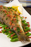 Fried trout. With bacon and green beans. Shallow DOF royalty free stock photography