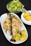 Fried trout with almonds. Served with fresh spinach salad and potatoes Royalty Free Stock Photo