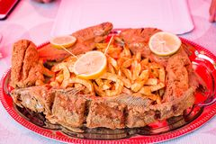 Fried trout fish and catfish pieces, fried potatoes, decorated with lemon slices on plate. Fresh fish from Tisza river. Delicious fried trout fish and catfish stock photography
