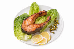 Fried trout with a piece of lettuce, lemon and green peas Stock Photo