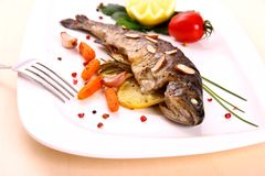Fried trout with vegetables and split almonds Royalty Free Stock Images