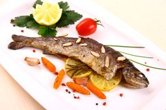 Fried trout with vegetables and split almonds on white plate Royalty Free Stock Images