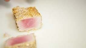 Fried tuna steak cutted with knife. With man's hands stock video footage