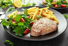 Fried Tuna Steaks on Black Plate with Fresh Green, Tomato Salad, lemon and french fries. healthy sea food Royalty Free Stock Images