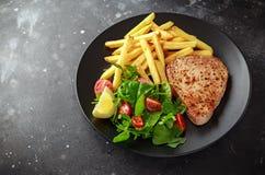 Fried Tuna Steaks en la placa negra con verde fresco, ensalada del tomate, el limón y las patatas fritas Alimento de mar sano imágenes de archivo libres de regalías