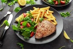 Fried Tuna Steaks på den svarta plattan med ny gräsplan, tomatsallad, citronen och fransmansmåfiskar sunt hav för mat Royaltyfri Foto