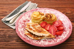 Fried turkey fillets, roasted potatoes and cherry tomato Stock Image