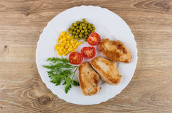 Fried turkey meat, greens, tomatoes, sweet corn, green peas. Pieces of fried turkey meat, greens, tomatoes, sweet corn, green peas in white dish on wooden table royalty free stock images