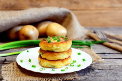 Fried vegetable cutlets. Potato cutlets with vegetables and spices on plate. Raw potatoes, fresh green onions, fork, knife Stock Image