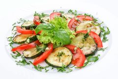 Fried vegetable marrows with greenery and tomatoes royalty free stock photos
