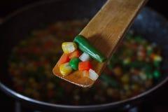 Fried vegetable mix on black skillet. Stewed sliced vegetables on a pan. Frozen vegan breakfast preparation. Using paddle. Fried vegetable mix on black skillet royalty free stock images
