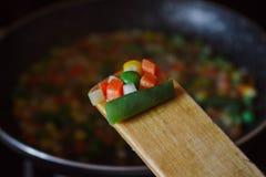 Fried vegetable mix on black skillet. Stewed sliced vegetables on a pan. Frozen vegan breakfast preparation. Using paddle. Fried vegetable mix on black skillet stock photography