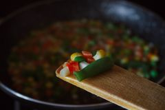 Fried vegetable mix on black skillet. Stewed sliced vegetables on a pan. Frozen vegan breakfast preparation. Using paddle. Fried vegetable mix on black skillet royalty free stock photo