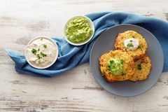 Fried vegetable rosti from cauliflower and parmesan cheese with. Two dips from sour cream and avocado, parsley garnish, blue plate and napkin on a bright wooden Stock Photography